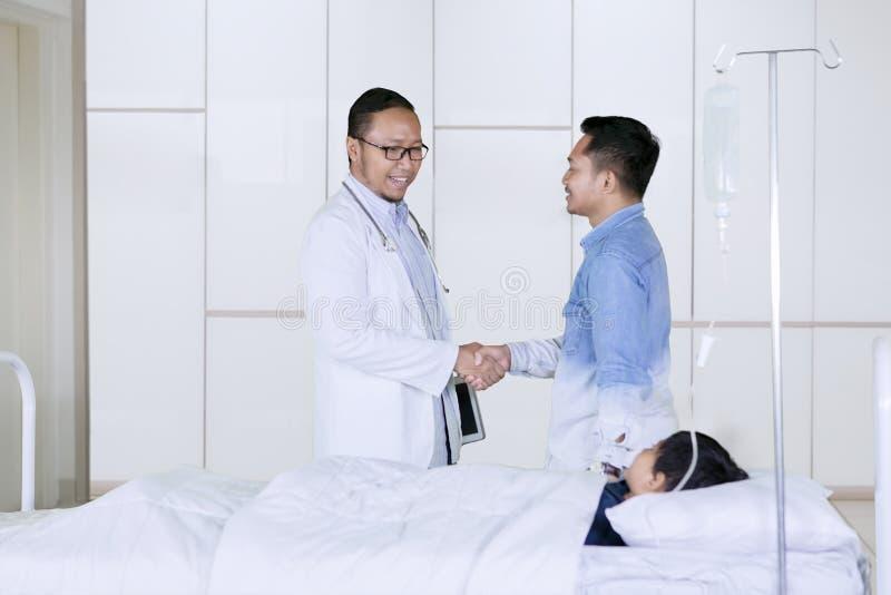 Doktorski handshaking z ojca pacjentem w szpitalu zdjęcie stock