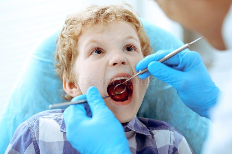 Doktorski i cierpliwy dziecko Chłopiec ma jego zęby egzamininujących z dentysta medycyną, opieką zdrowotną i stomatology pojęciem fotografia stock