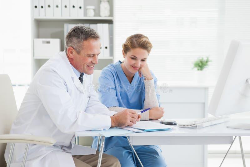 Doktorski i pielęgniarko czyta nad medycznymi notatkami fotografia stock