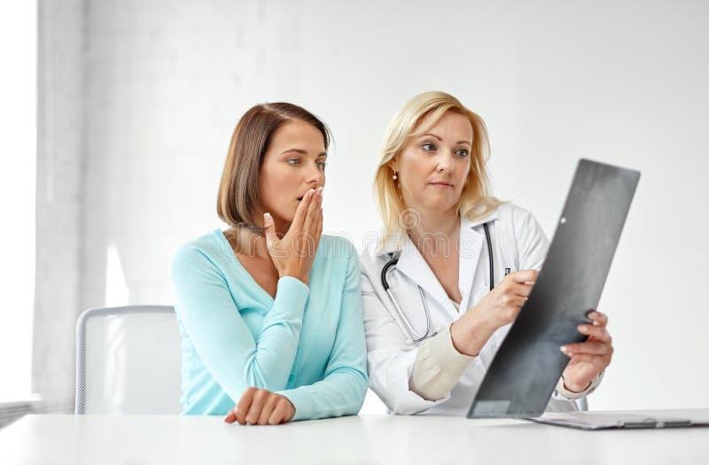 Doktorski i smutny kobieta pacjent z promieniowaniem rentgenowskim przy kliniką fotografia stock