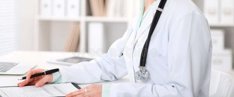 Doktorski kobiety obsiadanie przy biurkiem z komputerem przy miejsce pracy w szpitalnym biurze Niewiadome lekarz ręki w górę obraz royalty free