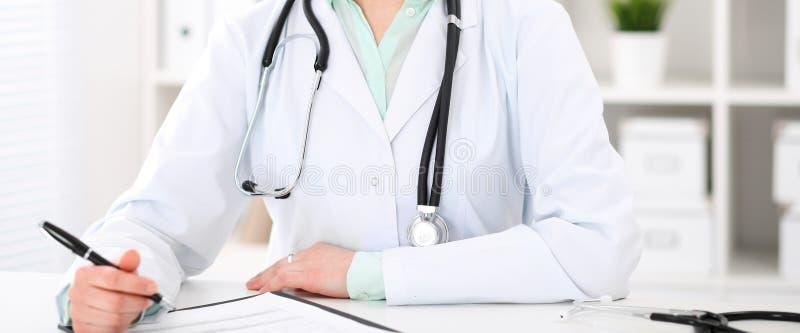 Doktorski kobiety obsiadanie przy biurkiem z komputerem przy miejsce pracy w szpitalnym biurze Niewiadome lekarz ręki w górę fotografia royalty free
