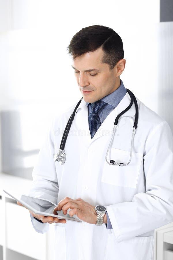 Doktorski mężczyzna używa pastylka komputer dla sieci badawczego lub wirtualnego choroby traktowania Doskonalić usługa zdrowotna  fotografia stock
