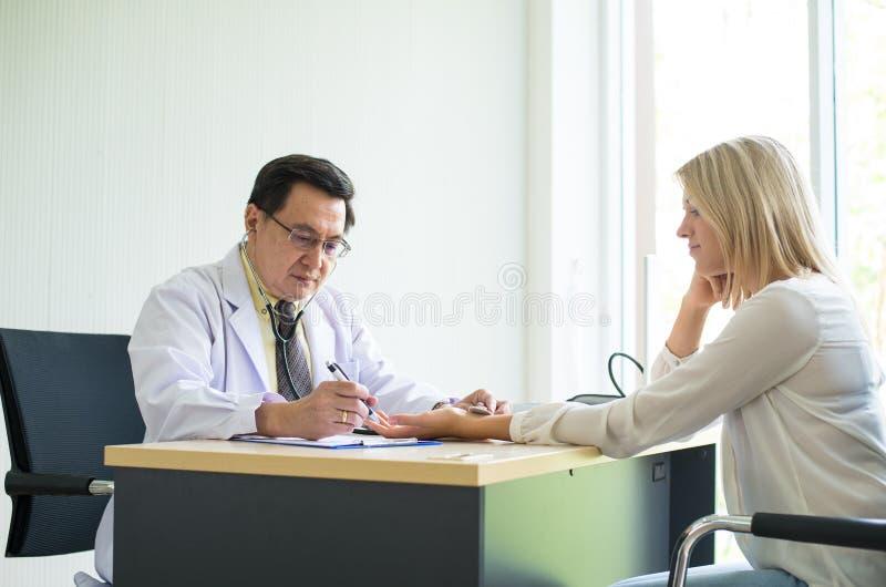 Doktorski męski używa stetoskop kobieta pacjent dla słuchającego tętna na sickbed przy szpitalem, Selekcyjnej ostrości ręka zdjęcia royalty free