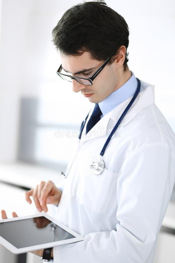 Doktorski m??czyzna u?ywa pastylka komputer dla sieci badawczego lub wirtualnego choroby traktowania Doskonali? us?uga zdrowotna  fotografia stock