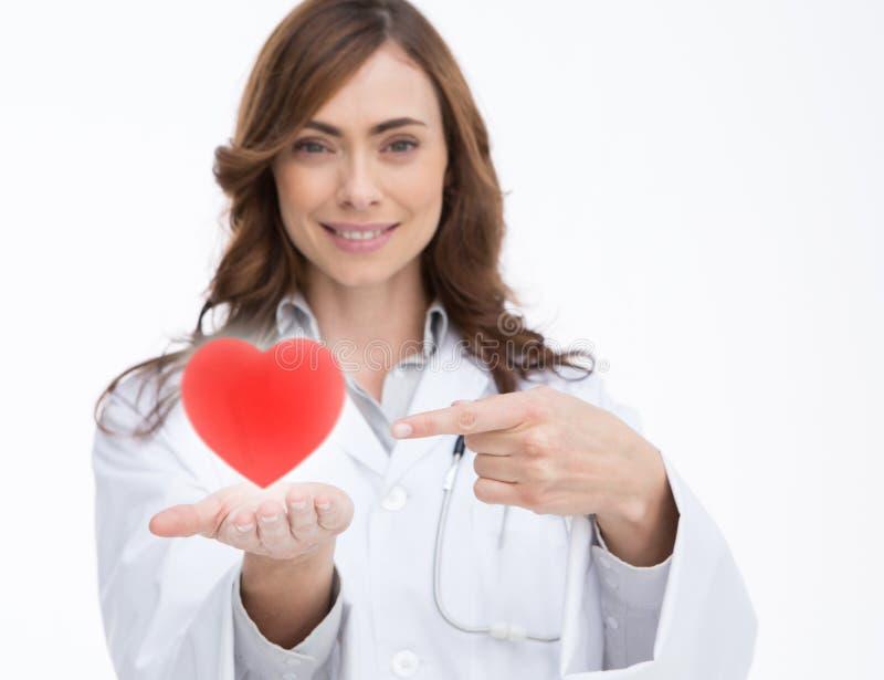 Doktorski mienie i wskazywać przy czerwonym sercem obrazy royalty free