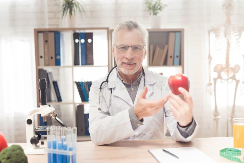 Doktorski obsiadanie przy biurkiem w biurze Lekarka trzyma świeżego czerwonego jabłka fotografia royalty free