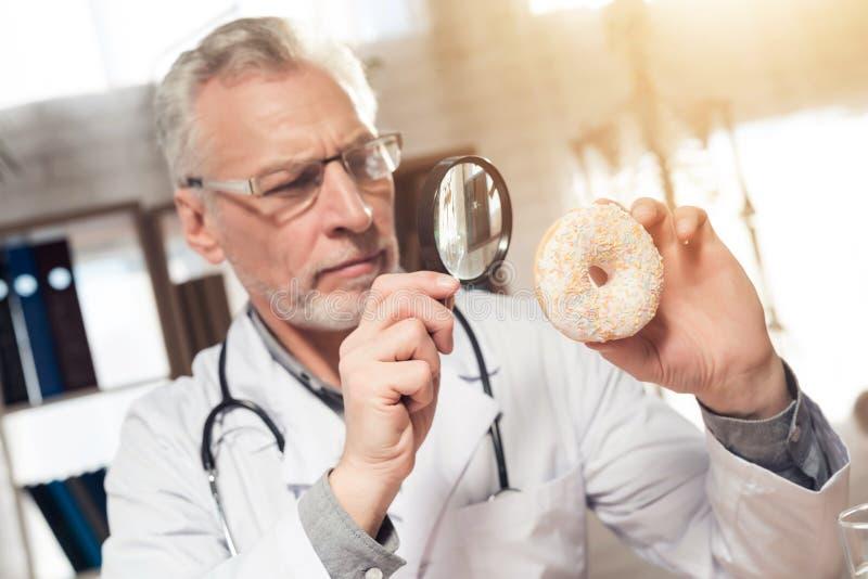 Doktorski obsiadanie przy biurkiem w biurze Mężczyzna jest przyglądającym pączkiem z powiększać - szkło fotografia stock
