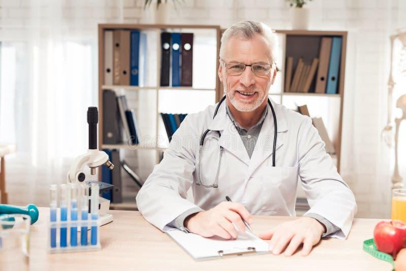 Doktorski obsiadanie przy biurkiem w biurze Mężczyzna pisze na schowku zdjęcia stock
