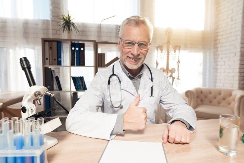 Doktorski obsiadanie przy biurkiem w biurze z mikroskopem i stetoskopem Mężczyzna daje aprobatom obraz stock