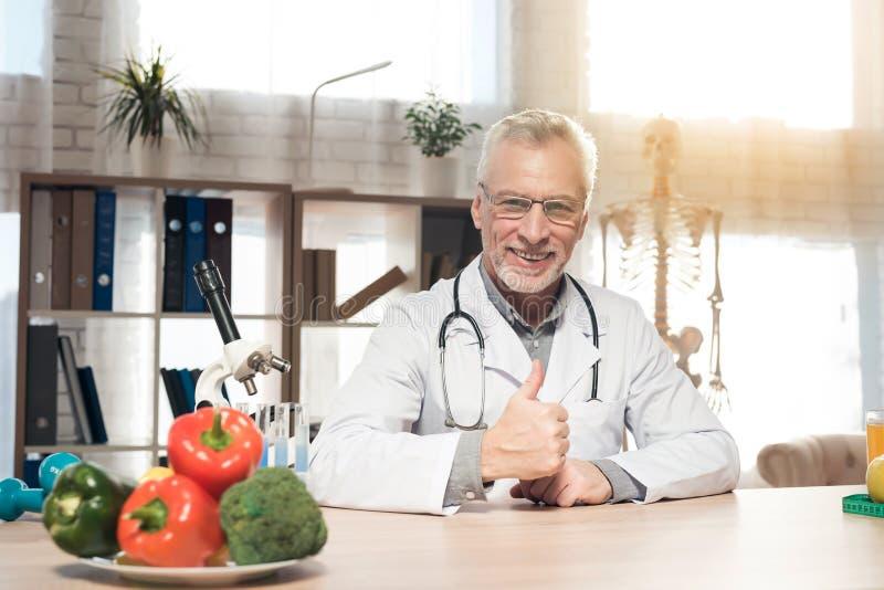 Doktorski obsiadanie przy biurkiem w biurze z mikroskopem i stetoskopem Mężczyzna daje aprobatom obraz royalty free