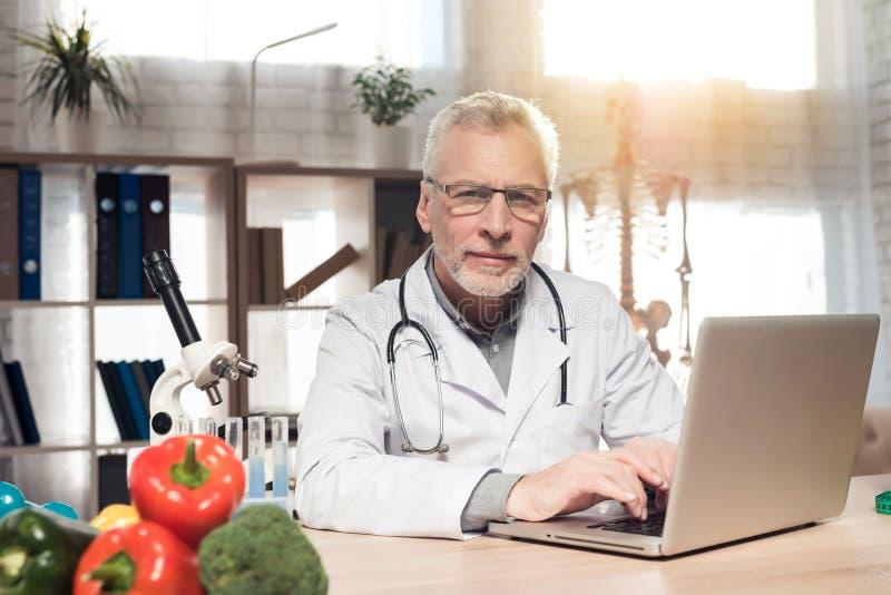 Doktorski obsiadanie przy biurkiem w biurze z mikroskopem i stetoskopem Mężczyzna pracuje na laptopie fotografia stock