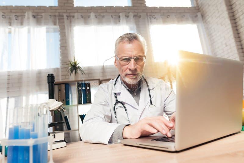 Doktorski obsiadanie przy biurkiem w biurze z mikroskopem i stetoskopem Mężczyzna pracuje na laptopie obrazy royalty free