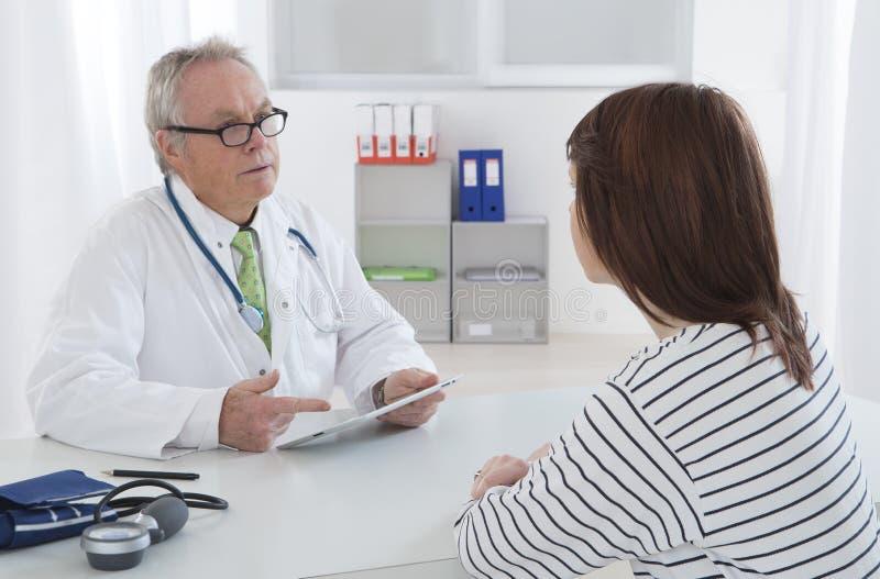 Doktorski opowiadać jego żeński młody pacjent przy biurem obraz royalty free