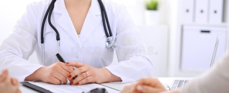 Doktorski opowiadać pacjent przy szpitalnym biurem Niewiadomy lekarz mówi o medycznych egzaminów rezultatach dla wybierać optymal zdjęcie stock
