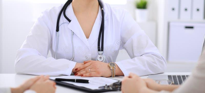 Doktorski opowiadać pacjent przy szpitalnym biurem Niewiadomy lekarz mówi o medycznych egzaminów rezultatach dla wybierać optymal fotografia stock