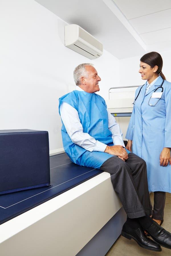Doktorski opowiadać senior przed kości gęstości pomiarem fotografia royalty free