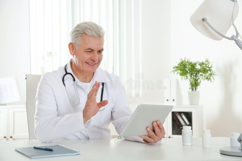 Doktorski ordynacyjny pacjent u?ywa wideo gadk? na pastylce obraz royalty free