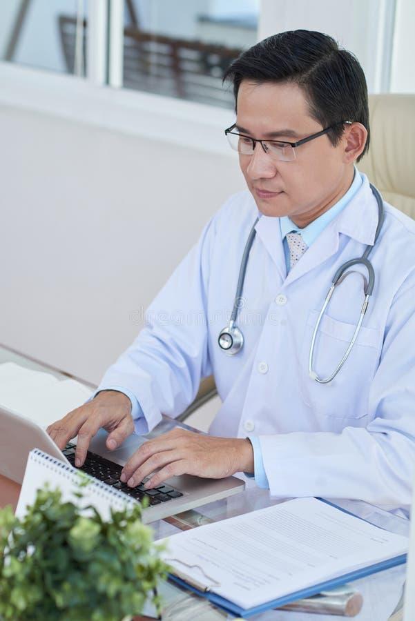 Doktorski pisać na maszynie na laptopie obraz royalty free