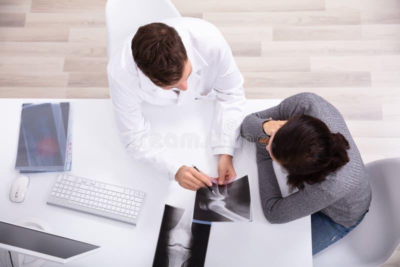 Doktorski Pokazuje Kolanowy promieniowanie rentgenowskie pacjent fotografia stock