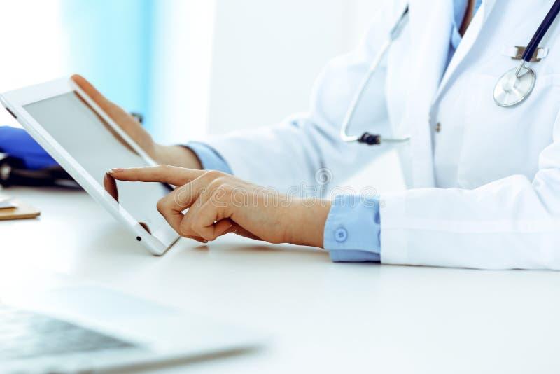Doktorski pracuj?cy st?? Kobieta lekarz u?ywa pastylka komputer w szpitalnym biurze w g?r? podczas gdy siedz?cy Opieka zdrowotna fotografia stock