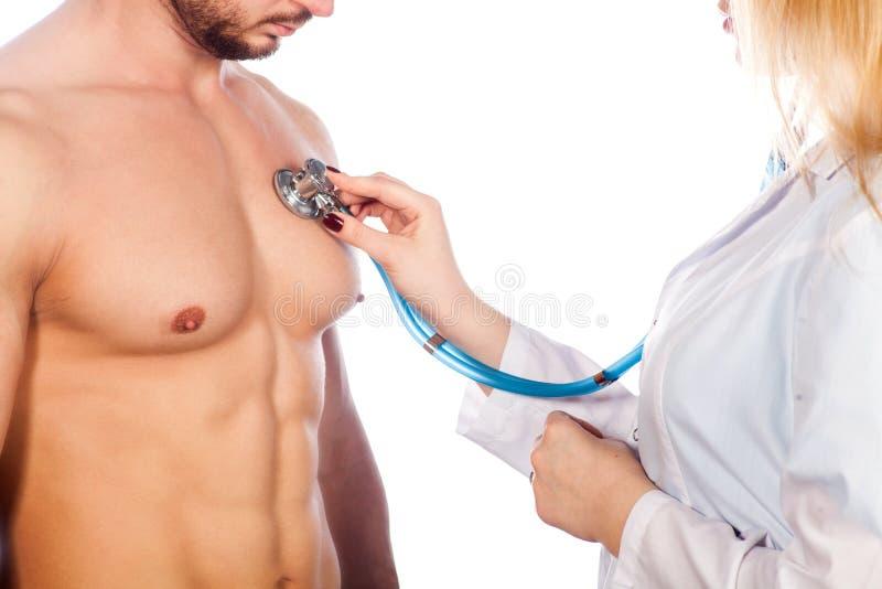 Doktorski słuchanie młoda cierpliwa klatka piersiowa z stetoskopem w jego biurze przy szpitalem zdjęcie stock
