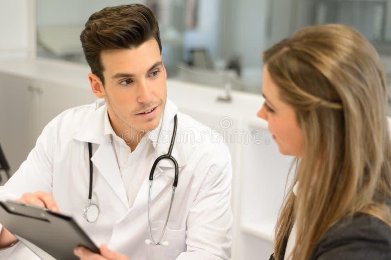 Doktorski słuchanie pacjent wyjaśnia ona bolesna w jego biurze obraz royalty free
