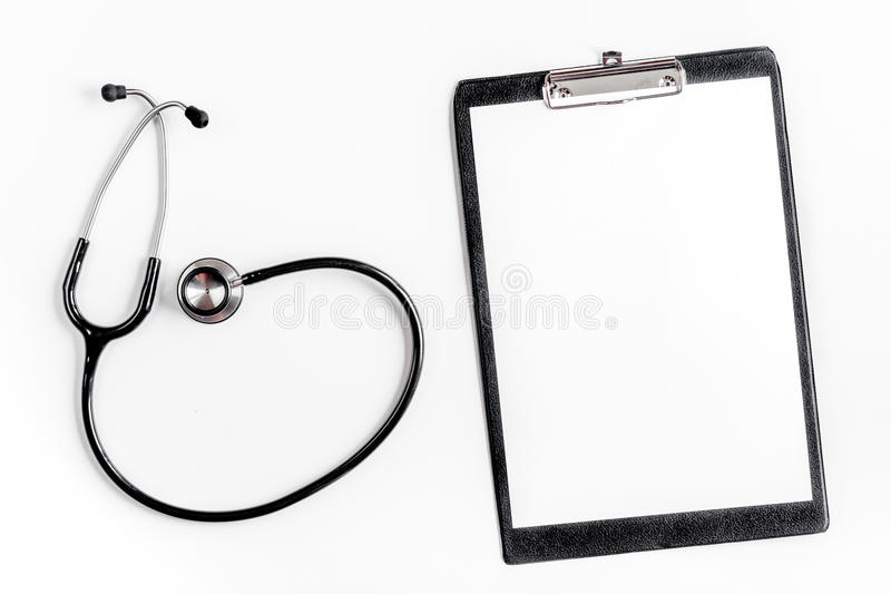 Doktorski ` s pracy biurko w szpitalu z notepad i stetoskopu tła odgórnego widoku białym mockup obrazy royalty free