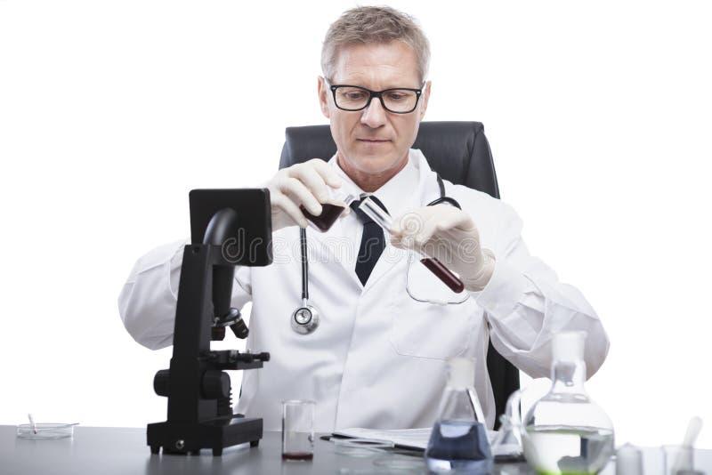 Doktorski spojrzenie i analizuje badanie krwi tubki obrazy stock