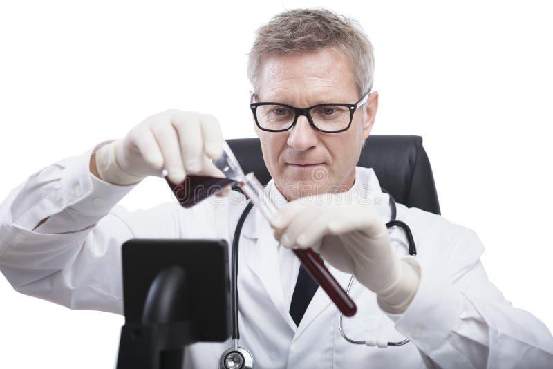 Doktorski spojrzenie i analizuje badanie krwi tubki fotografia royalty free