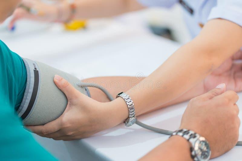 Doktorski sprawdza cierpliwy arterialny ciśnienie krwi w szpitalu tło zamazywał opieki pojęcia twarzy zdrowie maski pigułkę ochro zdjęcie stock