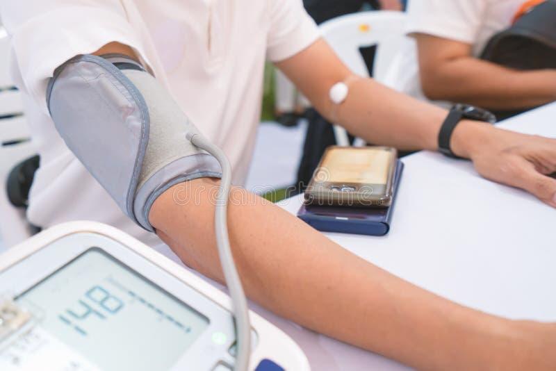 Doktorski sprawdza cierpliwy arterialny ciśnienie krwi w szpitalu tło zamazywał opieki pojęcia twarzy zdrowie maski pigułkę ochro obrazy stock