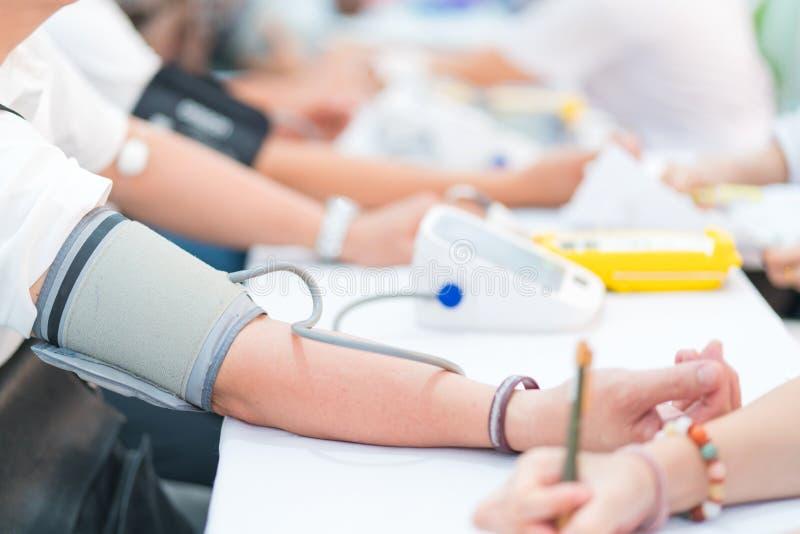 Doktorski sprawdza cierpliwy arterialny ciśnienie krwi w szpitalu tło zamazywał opieki pojęcia twarzy zdrowie maski pigułkę ochro zdjęcia royalty free