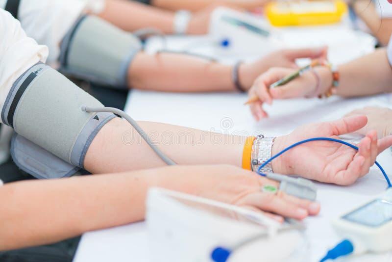 Doktorski sprawdza cierpliwy arterialny ci?nienie krwi w szpitalu t?o zamazywa? opieki poj?cia twarzy zdrowie maski pigu?k? ochro obrazy stock