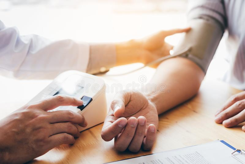 Doktorski używa stetoskop bierze klepnięcie na cierpliwej ` s ręki i odciskanie ciśnieniowego wymiernika guziku fotografia stock