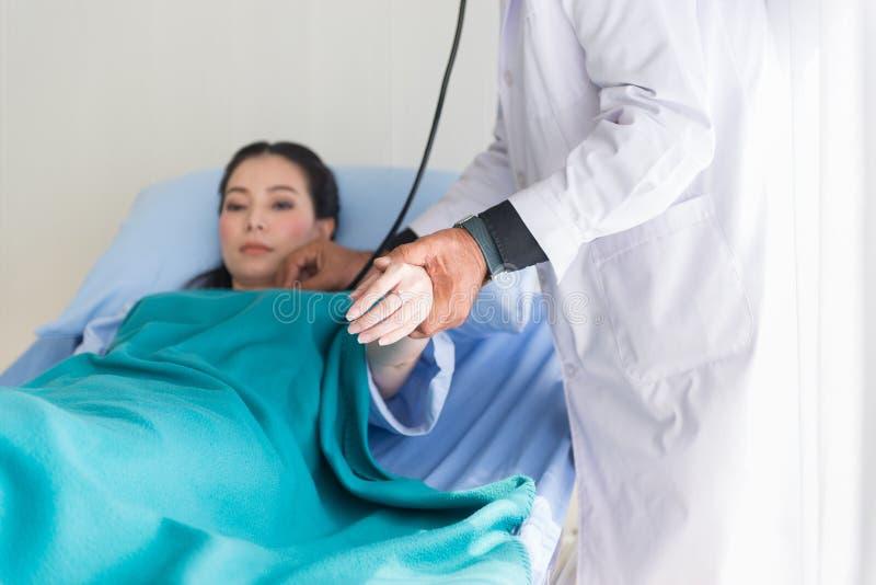 Doktorski używa stetoskop kobieta pacjent dla słuchającego tętna na sickbed przy szpitalem, Selekcyjnej ostrości ręka obrazy royalty free