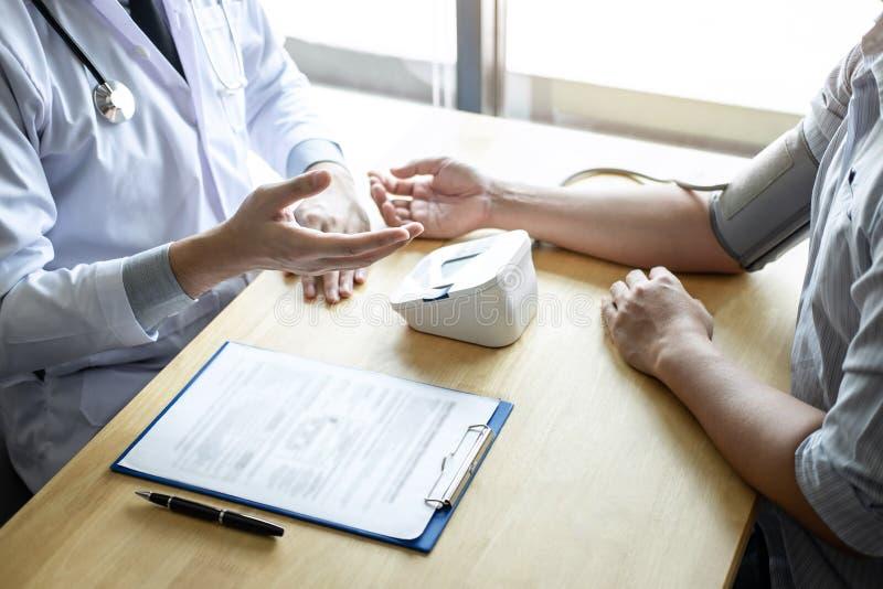 Doktorski używać pomiarowego ciśnienie krwi sprawdza pacjenta z egzamininować, przedstawiający wynika objaw i poleca traktowanie  obraz royalty free