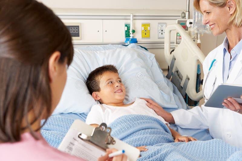 Doktorski Używa Cyfrowego Notepad Podczas gdy Odwiedzający dziecko pacjenta obrazy stock