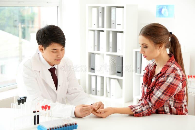 Doktorski używa lancet dostawać próbkę krwi dla testa w szpitalu obraz royalty free