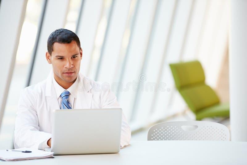 Doktorski Używa laptopu obsiadanie Przy biurkiem W Nowożytnym szpitalu zdjęcie stock