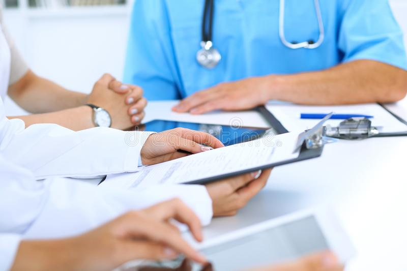 Doktorski używa pastylka komputer przy medycznym spotkaniem, zbliżenie Grupa koledzy przy tłem fotografia royalty free
