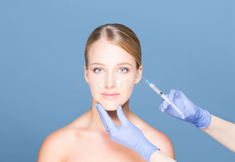 Doktorski wstrzykiwania botox w pięknej twarzy młoda kobieta Śliwki zdjęcie royalty free
