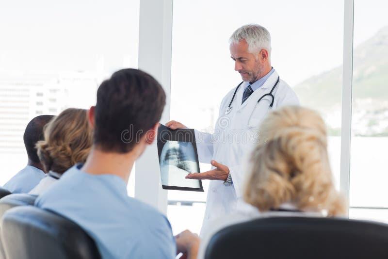 Doktorski wyjaśnia promieniowanie rentgenowskie jego drużyna zdjęcie royalty free