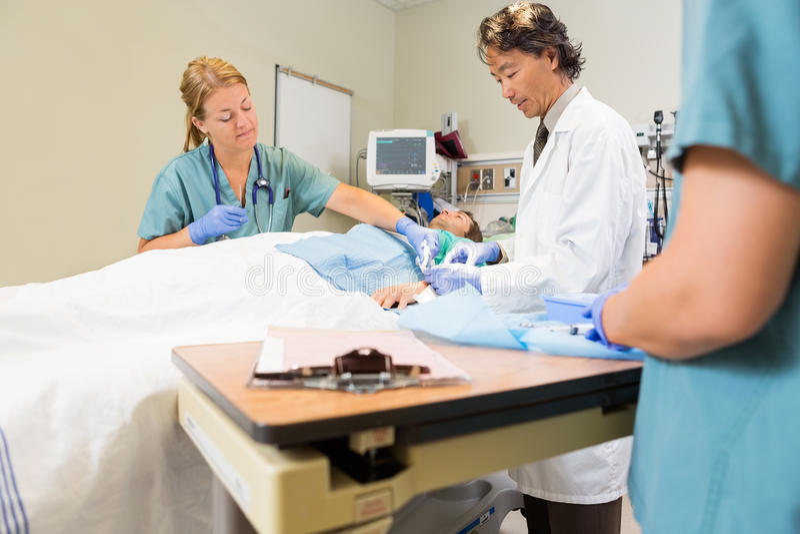 Doktorskiego zaszywania pacjenta Męska rana Podczas gdy pielęgniarka fotografia stock