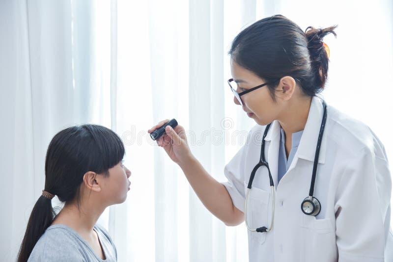 Doktorskläderexponeringsglas som kontrollerar flickapatienten, synar lite arkivbild