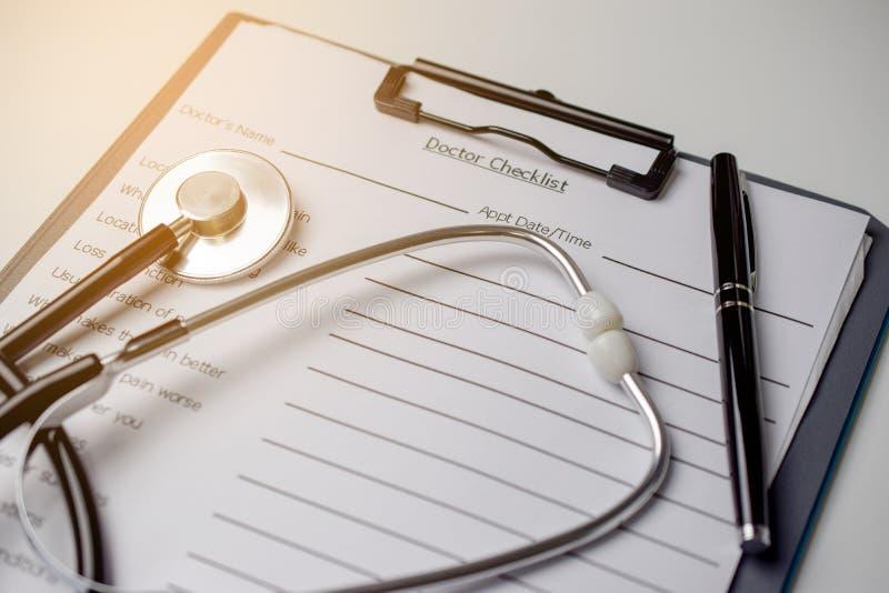 Doktorskontrolllista med stetoskopet och pennan arkivfoton