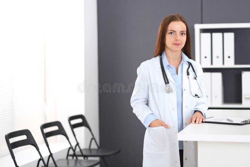 Doktorskvinna på arbete Stående av den kvinnliga läkaren som står det near mottagandeskrivbordet på kliniken eller nödlägesjukhus royaltyfria foton