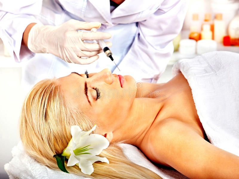 Doktorskvinna som ger botoxinjektioner. royaltyfria foton