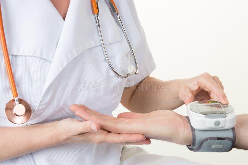 Doktorskvinna som mäter arteriellt blodtryck i sjukhus- och medicinbegrepp arkivfoto