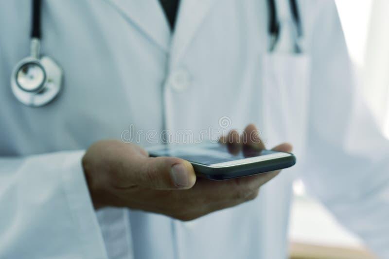Doktorsman som använder en smartphone arkivfoton